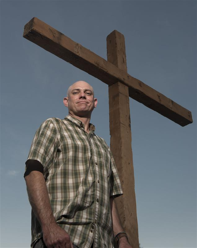 Chris poses by a crucifix