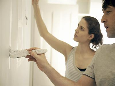 Couple painting new apartment